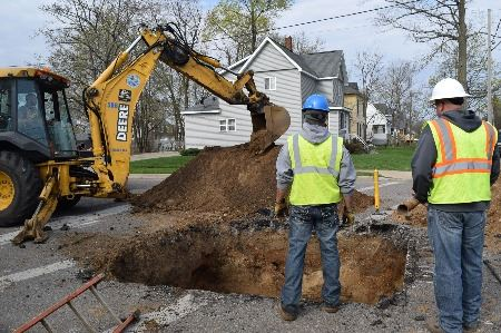 Two men in work vests and hard hats stand next to hole in street, with excavator nearby